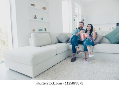 Ha-ha! Happiness joy pleasure enjoyment cinema concept. Full size portrait of positive laughters watching funny comedy eating snack sitting on sofa in modern white living room