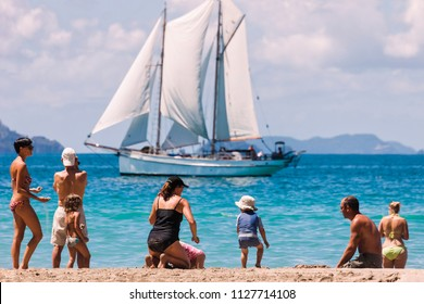 HAHEI, NEW ZEALAND – JANUARY 5, 2009: People looking at sailing ship on beach of Cathedral Cove in Hahei, New Zealand
