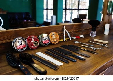 Hai, Ukraine - 08 November, 2017: Dapper Dan and Upperut hair waxes or clays or pomades, combs and scissors on the wooden surface in barbershop.