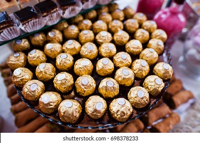Hai, Ukraine - August 10, 2017: close-up photo of delicious pralines in golden wrap called Ferrero Rocher laying on the table in restaurant.