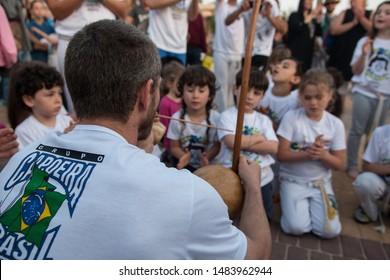 Haifa, Israel - April 28th 2019: Roda (Capoeira circle) at the beach promenade. Teacher playing the Berimbau for young children.