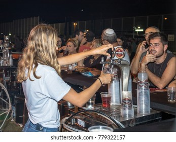 Haifa, Israel, August 16, 2017 : The seller pours cold fresh beer to the visitor in a plastic glass at the traditional annual beer festival in the city of Haifa in Israel