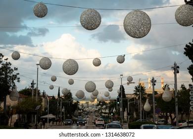 Haifa, Israel - December 27, 2018: Christmas decoration on David Ben Gurion Avenue, German Colony, against cloudy sky at the dusk in Haifa, Israel.