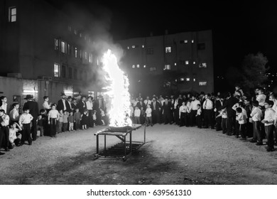 HAIFA, ISRAEL - MAY 13, 2017: A crowd of ultra-orthodox Jews gather around a fire, as part of the Lag BaOmer holiday celebration, in Haifa, Israel