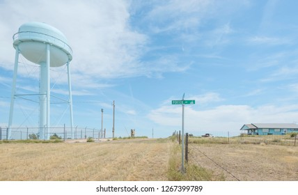 Haigler, Nebraska, USA. Porter Avenue and elevated water tank with wooden house on a hot summer day in the small town of Haigler, Nebraska, USA.