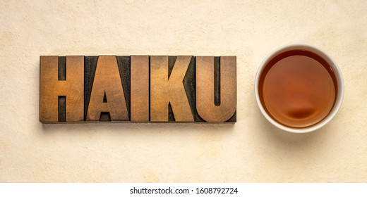 haiku  - a very short form of Japanese poetry - word abstract in vintage letterpress printing blocks against handmade paper with a cup of tea