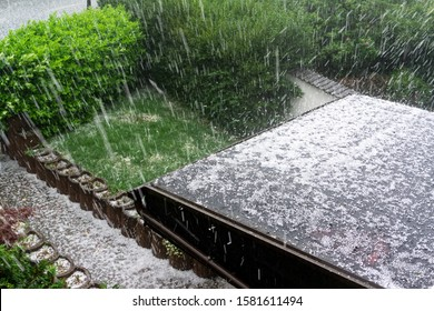 Hail falls on a house roof during a hailstorm