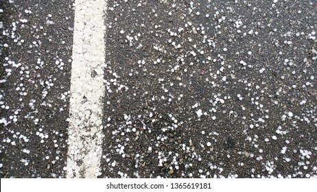 Hail on the ground after hailstorm. Hail balls falling in a big puddle on urban asphalt in the town. Bad weather in summer city.