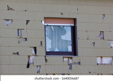 hail and storm damage at house wall, stormy weather, Holes in exterior siding in home from damage by hail storm , climate change, danger
