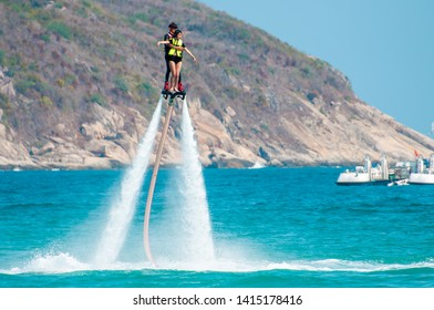Hainan, Sanya, China - May 14, 2019: Flyboarding. Flying over the water on the board with a powerful jet of water. Attraction on the beach. Extreme sport and recreation