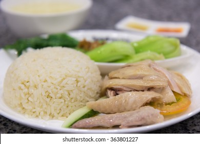 Hainanese Chicken Rice in Singapore. Most favorite famous Chinese food in Singapore. Steamed rice, chicken broth soup, serve with steam juicy chicken meat on white dish. Chicken, Vegetables with rice