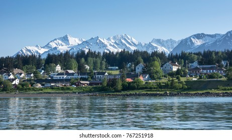 Haines Alaska from across the water with snow on the mountains.