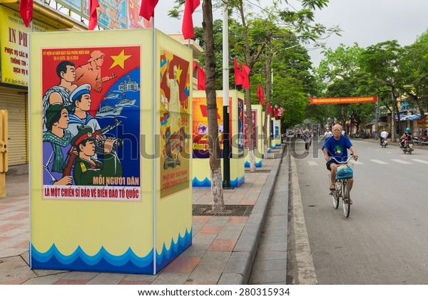 Haiphong, Vietnam - Apr 30, 2015: A man cycles on street passing Reunification Day Propaganda. Reunification Day marks the event when North Vietnamese troops captured Saigon on April 30, 1975