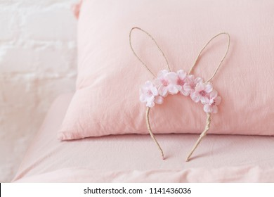 Hair accessory bunny ears with sakura flowers on pink background
