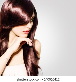 Hair. Beautiful Brunette Girl with Healthy Long Brown Hair. Beauty Model Woman Portrait isolated on White Background. Hairstyle. Stylish Haircut. Fringe. Glossy Smooth Fashion Hair. Extensions