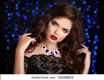 Hair. Beautiful Sexy Brunette Woman. Red lips makeup. Fashion gems necklace jewelry. Healthy Long Brown Curly Hairstyle. Beauty Model Girl over party blue lights background.