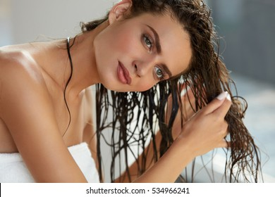 Hair And Body Care. Portrait Of Beautiful Young Female Model After Bath Applying Hair Oil. Closeup Of Sexy Woman In Towel Drying Wet Long Hair. Health And Beauty Concept. High Resolution Image