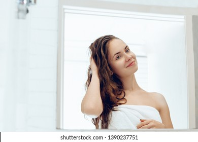 Hair and body care. Woman touching hair and smiling while looking in the mirror.Portrait of happy girl with wet hair in bathroom applying conditioner and oil. Girl uses protection moisturizing cream
