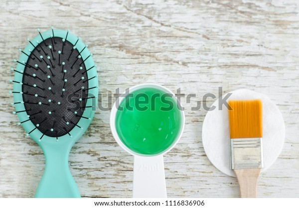Hair brush and small scoop with green gel hair mask (conditioner) with spirulina, aloe vera and marine collagen extracts. Spa and natural skin and hair care concept. Top view, copy space.