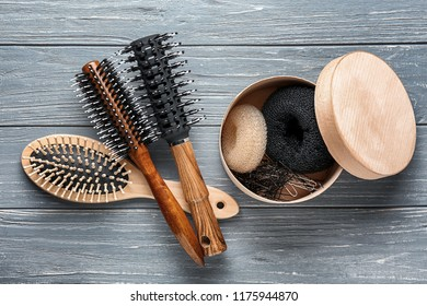 Hair brushes with doughnuts and pins on wooden background