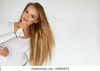 Hair Care. Beautiful Smiling Woman Drying Healthy Long Straight Hair Using Hair Dryer. Portrait Of Attractive Girl With Blonde Hair Using Hairdryer. Hairstyle, Hairdressing Concept. High Resolution