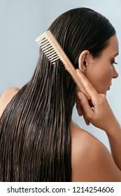 Hair Care. Beautiful Woman Brushing Wet Long Hair After Bath