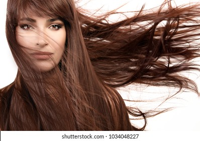 Hair care and beauty concept. Beautiful model girl wearing subtle makeup with gorgeous healthy long hair blowing to the side in a breeze. Beauty portrait isolated on white in a close up cropped view
