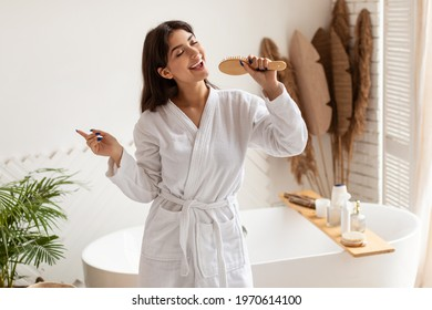 Hair Care. Cheerful Brunette Lady Singing Posing With Hairbrush Having Fun In Modern Bathroom Indoor. Haircare Cosmetics Advertisement. Beauty Rituals Concept