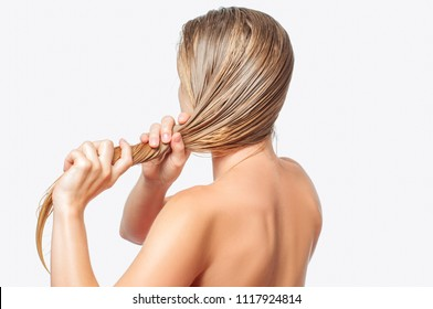 Hair care concept. Blond woman with long wet hair is applying hair conditioner