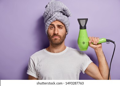 Hair care and grooming concept. Sleepy man holds hairdryer, going to make hairstyle after taking shower, wears soft towel on head, white t shirt, poses against purple background ready for drying hair.
