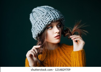 Hair care, health, beauty, split ends, advertising concept. Close up studio portrait of young sad, thoughtful girl holding her hair, braids posing on dark background. Copy, empty space for text