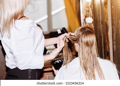Hair care in modern spa salon.Young attractive woman with cute smile looking at herself in mirror at beauty salon, pleased with work of professional hairdresser.