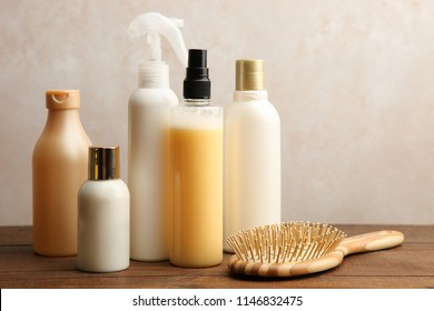 Hair care products on a wooden table on a neutral background.