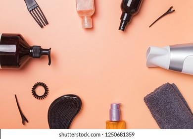 Hair care produts and styling items on orange background, top view. Beauty salon concept
