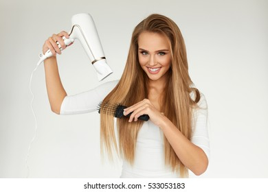 Hair Care. Woman Drying Beautiful Long Straight Hair Using Dryer. Portrait  Of Attractive Girl ea6429d3f
