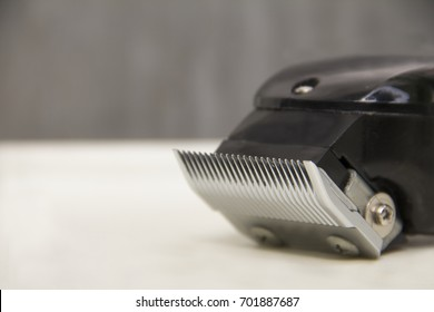 Hair clipper's blade.Picture of metal blade on hair clipper or Battalion put on white stand. Metallic and black color with exposed concrete wall background.