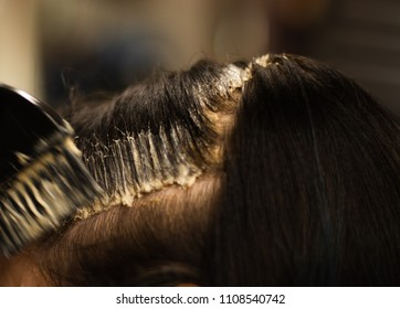Hair color being applied to roots during a retouch process