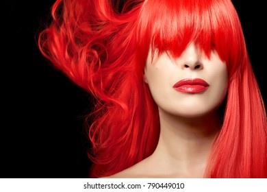 Hair color concept of young red-haired woman with long fringe and red lipstick against black background