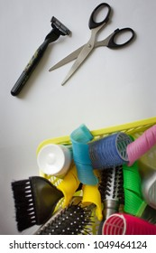 Hair curlers and combs in a basket with garbage. Next scissors and a razor. A simple solution to the problem, a radical approach. Vertical arrangement.