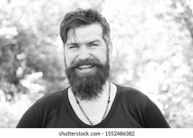 Hair cut for your face shape. Happy guy with shaped beard and styled hair. Hairy hipster with stylish beard and mustache hair on natural background. Bearded man smiling with unshaven face hair.