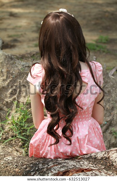 Hair and dress fashion style, back of Women in pink polka dot dress sit in the wood