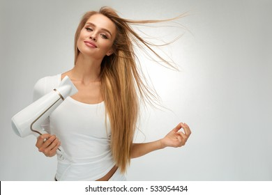 Hair Dryer. Beautiful Smiling Girl With Blonde Long Straight Hair Using Hairdryer. Portrait Of Happy Female Using Blow Hair Dryer. Hairstyle, Hair Care Concept. High Resolution