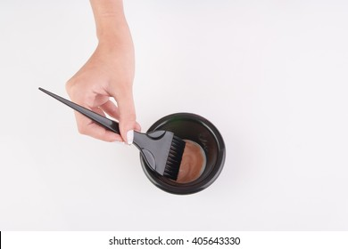 hair dye mixing bowl and brush with hand on white background