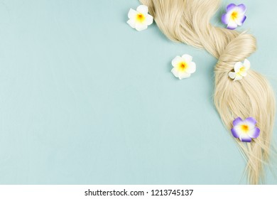 Hair extensions on blue wooden background. Top view