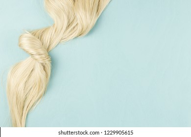 Hair extensions on blue wooden background. Top view, flat lay
