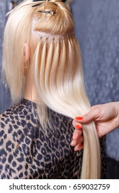 Hair extensions procedure. Hairdresser does hair extensions to young girl, blonde in a beauty salon. Selective focus
