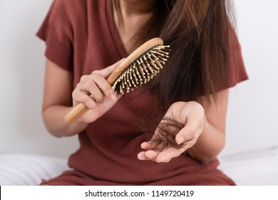 Hair fall problem. Young asian woman with comb and problem hair on white background. Beautiful girl looking hair loss from comb. Hair care and beauty concepts.