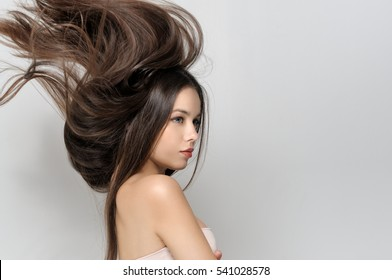 Hair fly up from the wind. Beautiful woman with bare shoulders has a clean well-groomed skin and long straight hair. Close-up portrait against a light gray background.