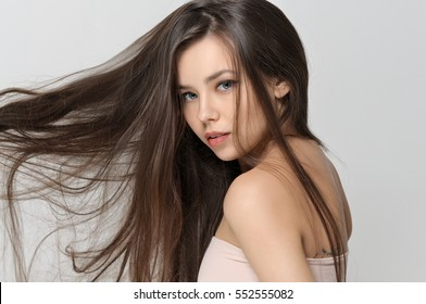Hair of the girl flutter in the wind. She has a clean well-groomed skin and long brown hair. Close-up portrait against a light gray background.