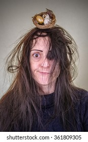 Hair like a bird's nest. Woman with messy hair and a birds nest containing eggs. Portrait.